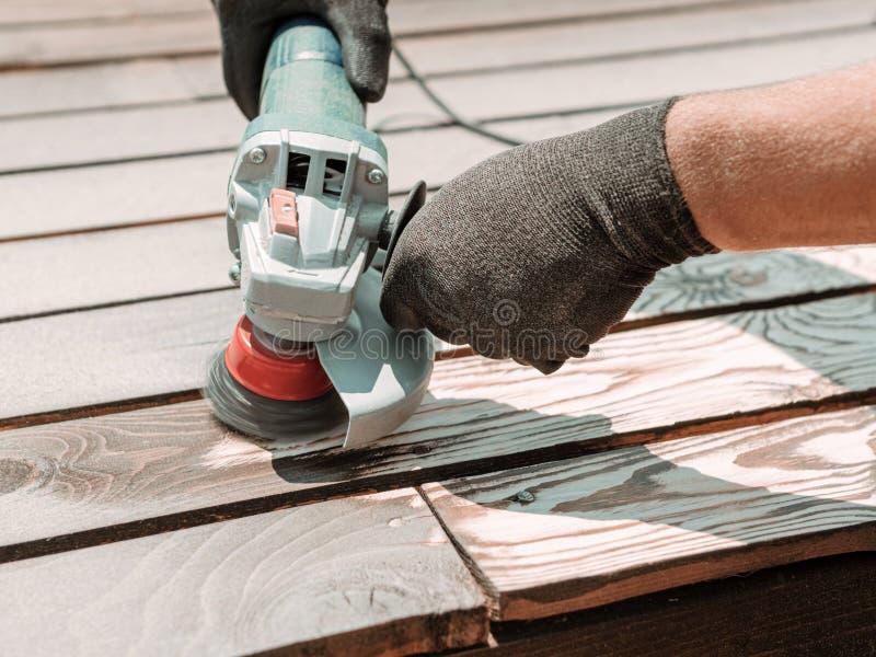 Homme de processus de travail de plan rapproché polissant la planche en bois foncée avec une brosse de broyeur et en métal d'angl image libre de droits