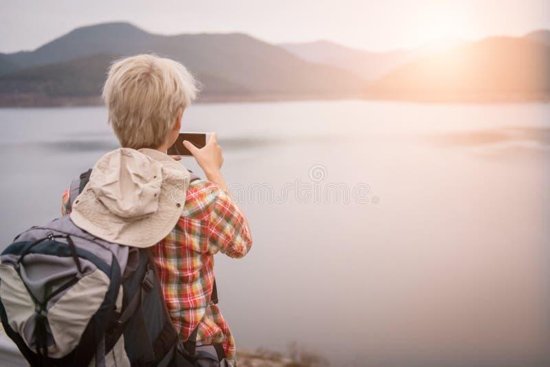 Homme de randonneur de voyageur avec le sac à dos augmentant près du lac backp de touristes photo libre de droits