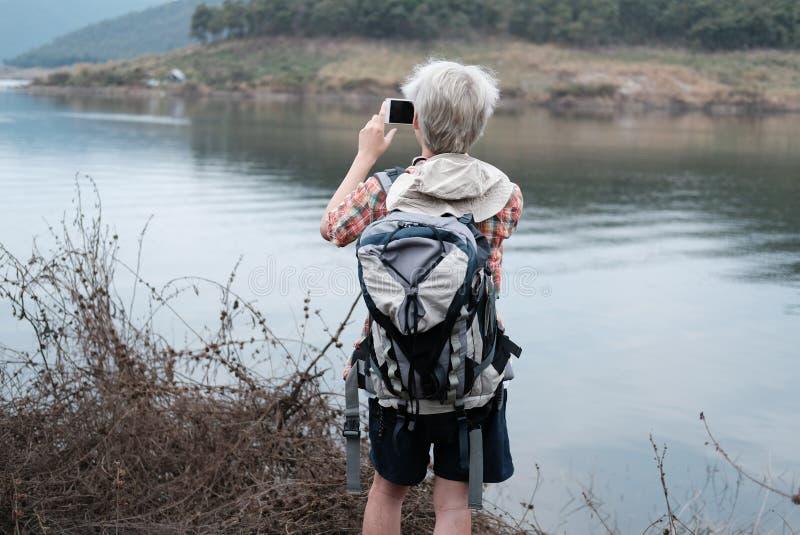 Homme de randonneur de voyageur avec le sac à dos augmentant près du lac backp de touristes photos stock
