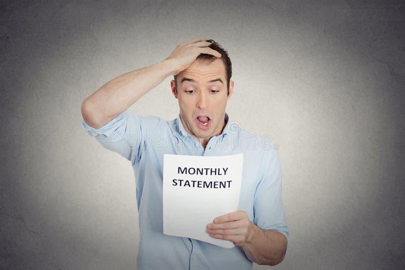 Homme de regard drôle choqué dégoûté à son relevé mensuel d'entreprise image stock