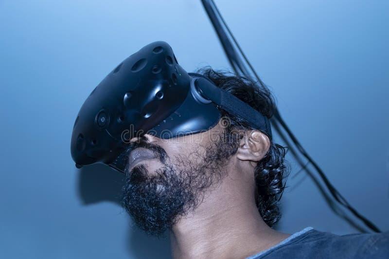 Homme de regard indien utilisant la technologie de VR sur la lumière bleue image stock