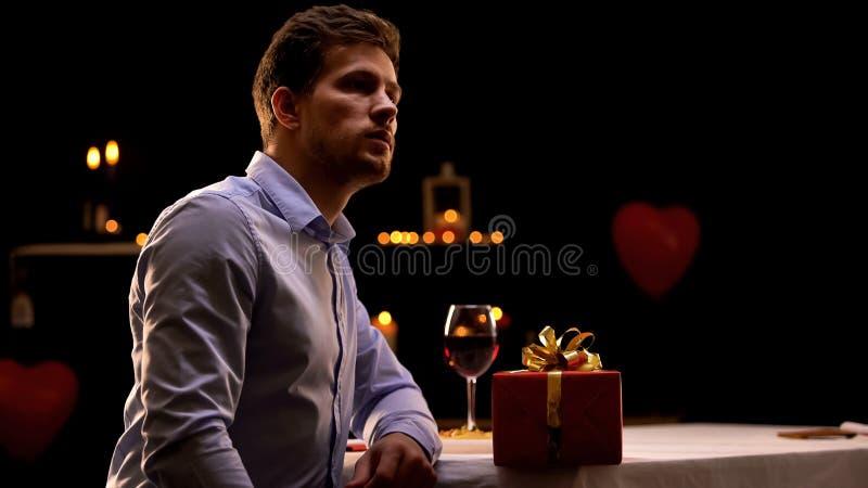 Homme de renversement s'asseyant dans le restaurant avec le boîte-cadeau rouge, date absente d'amie image stock