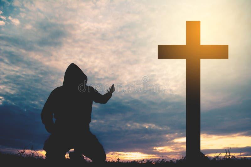 Homme de silhouette priant avec la croix photo stock