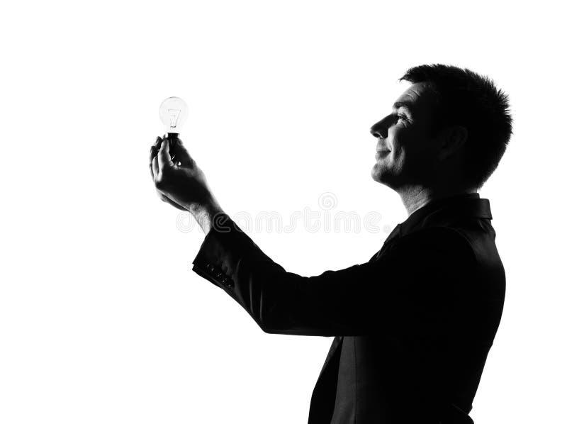 Homme de silhouette retenant l'ampoule image libre de droits