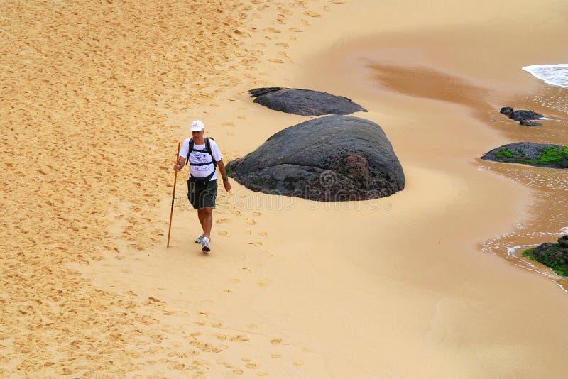 Homme de solitaire marchant par la plage images stock