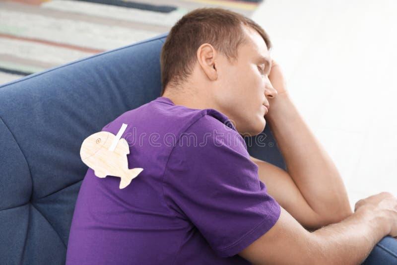 Homme de sommeil avec des poissons de papier attachés au sien de retour image libre de droits