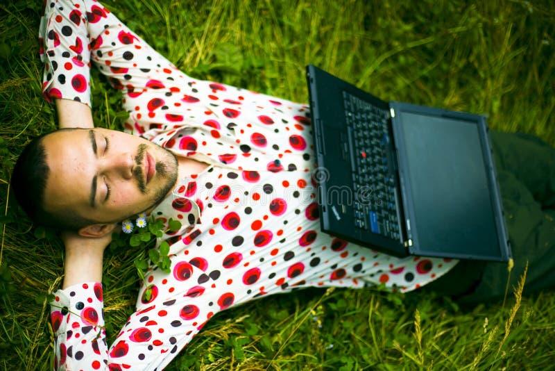 Homme de sommeil avec l'ordinateur portatif photos stock