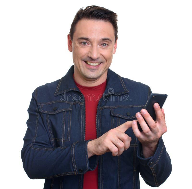 Homme de sourire à l'aide du téléphone portable d'isolement sur le blanc photographie stock libre de droits