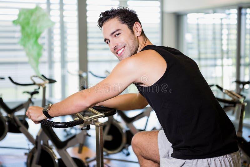 Homme de sourire à l'aide du vélo d'exercice image stock