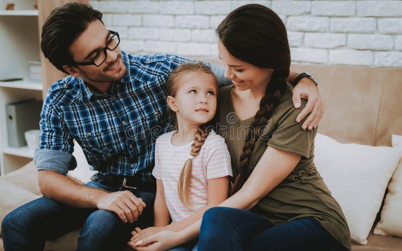 Homme de sourire étreignant la fille et la femme sur le sofa de Brown photos stock