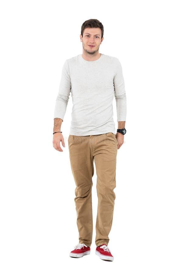 Homme de sourire amical dans le pantalon beige marchant vers l'appareil-photo image stock