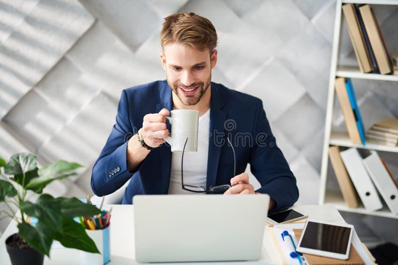 Homme de sourire appréciant la boisson chaude dans le bureau images libres de droits