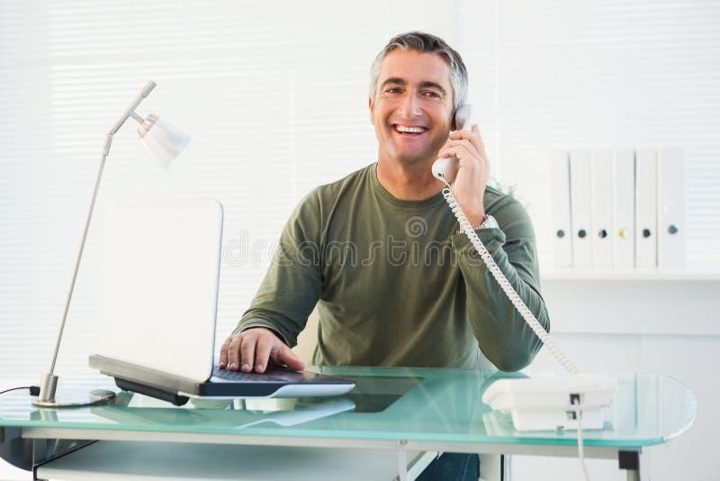 Homme de sourire au téléphone utilisant l'ordinateur portable image libre de droits