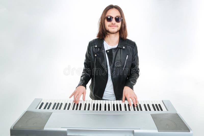 Homme de sourire avec de longs cheveux dans des lunettes de soleil jouant sur le synthétiseur photo stock