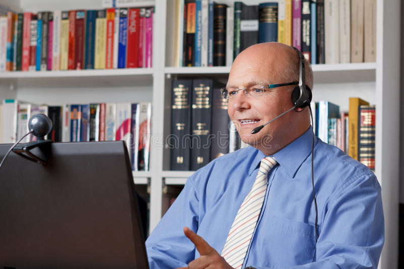 Homme de sourire avec des écouteurs, ordinateur photos stock