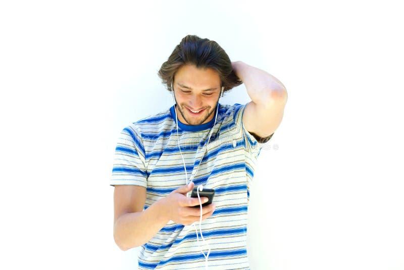 Homme de sourire avec la barbe et écouteurs écoutant la musique images libres de droits