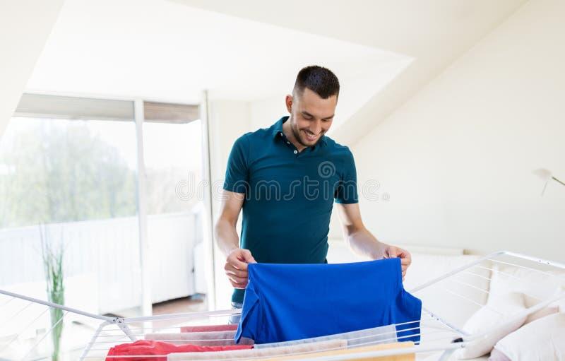 Homme de sourire avec la blanchisserie et le support de séchage à la maison image stock
