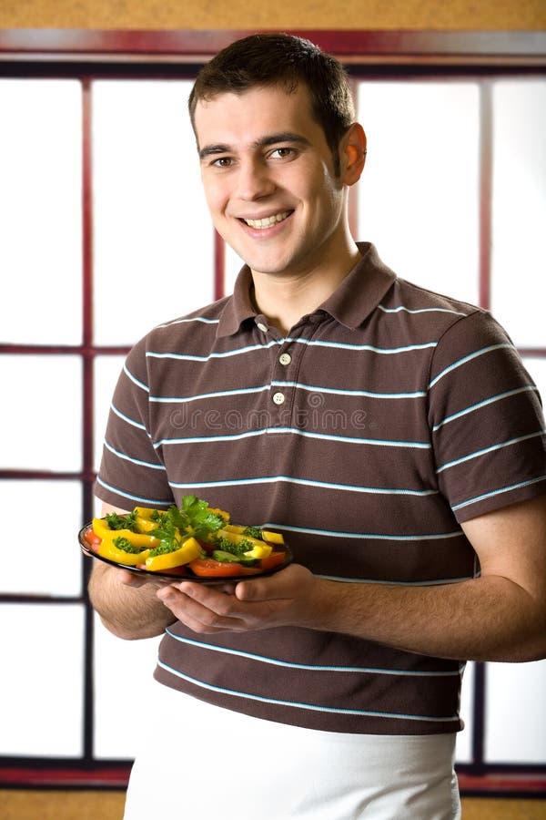 Homme de sourire avec la plaque de salade image libre de droits