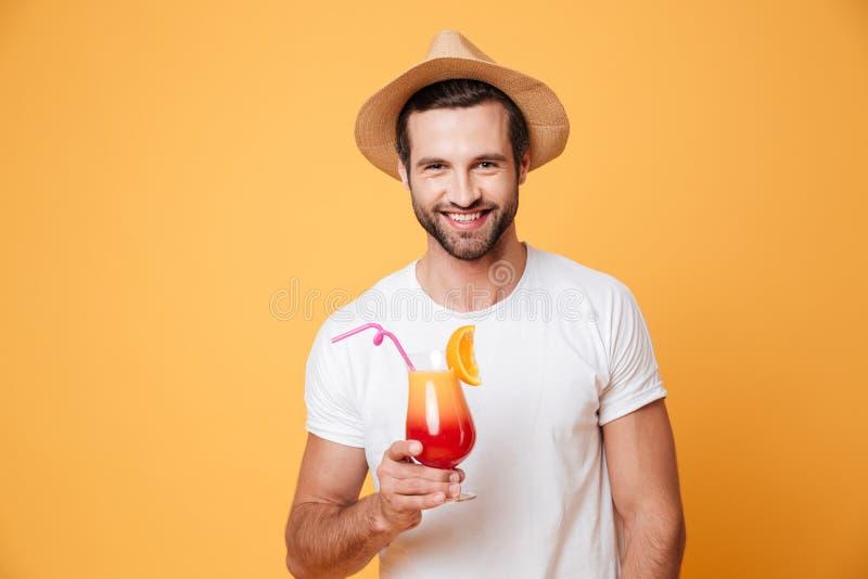 Homme de sourire avec le cocktail regardant l'appareil-photo photographie stock libre de droits