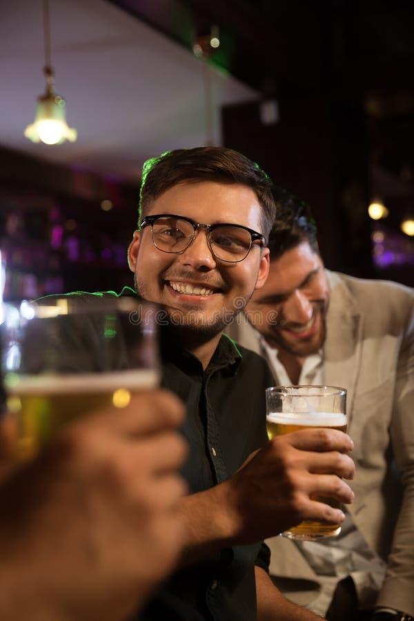 Homme de sourire ayant la bière avec ses amis dans un bar photographie stock