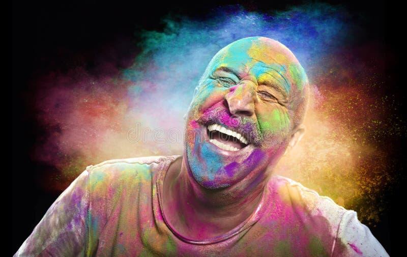 Homme de sourire chauve avec le visage coloré ayant l'amusement Colore le festival photo stock