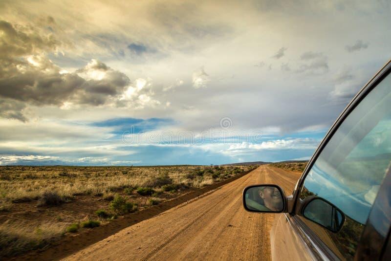 Homme de sourire conduisant par la région sauvage sur le chemin de terre image stock