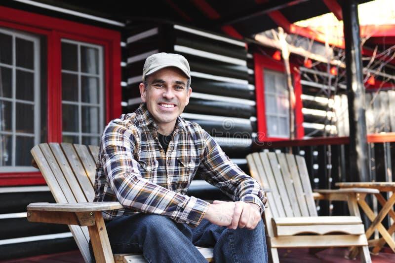Homme de sourire détendant au cottage photo stock