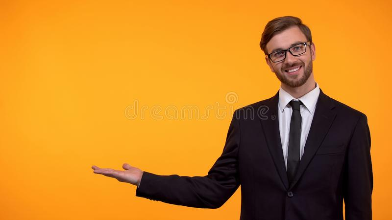 Homme de sourire d'affaires dirigeant des mains sur le fond orange, endroit pour le calibre image stock