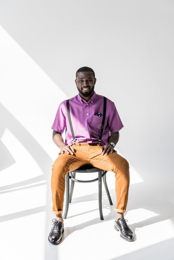 homme de sourire d'afro-américain dans l'habillement à la mode se reposant sur la chaise photographie stock