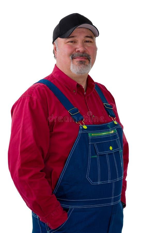 Homme de sourire dans la salopette sur le fond blanc photographie stock