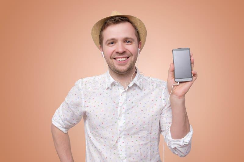 Homme de sourire dans le t?l?phone portable de participation de chapeau d'?t? photographie stock