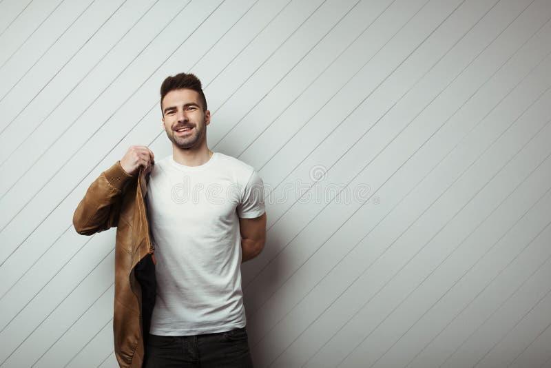 Homme de sourire dans le T-shirt et la veste vides, fond en bois blanc de mur photos stock