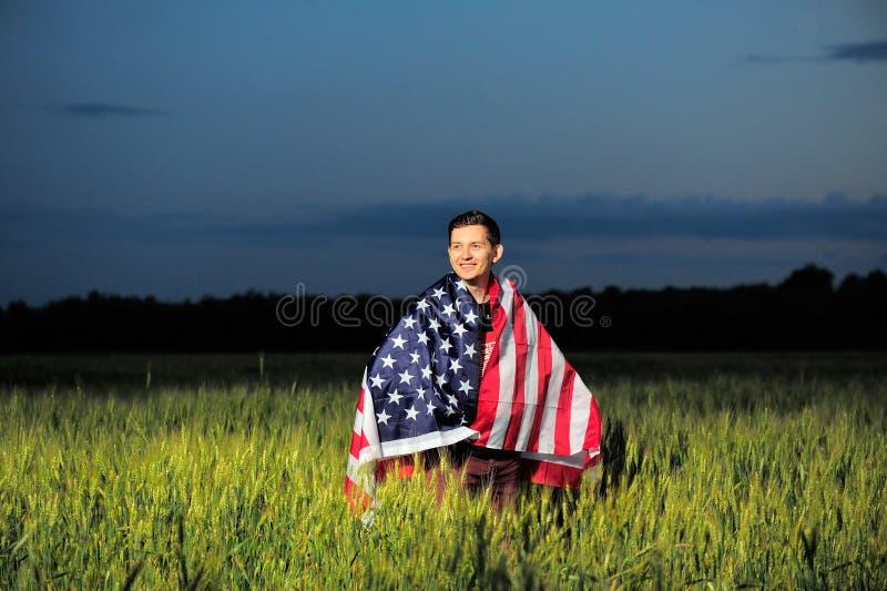 Homme de sourire dans un domaine de blé avec le drapeau américain photographie stock