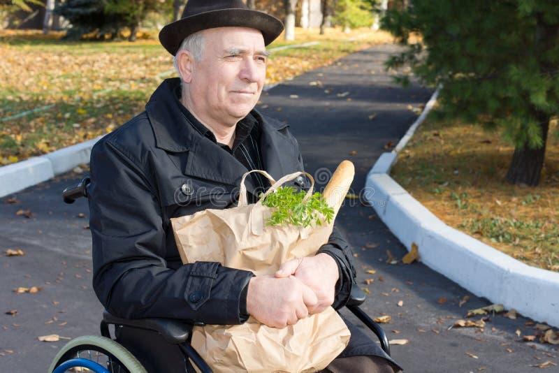 Homme de sourire dans un fauteuil roulant avec ses épiceries photo libre de droits