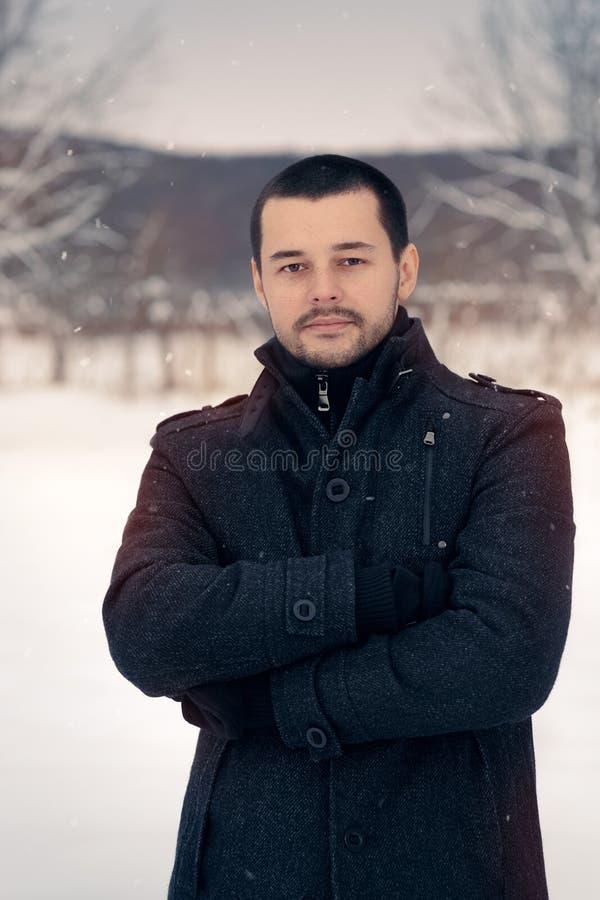 Homme de sourire dehors en décor de chute de neige d'hiver image stock