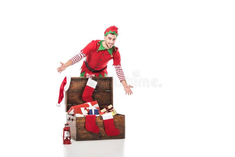 homme de sourire enthousiaste dans la position de costume d'elfe de Noël près du coffre en bois complètement des présents d'isole photo libre de droits