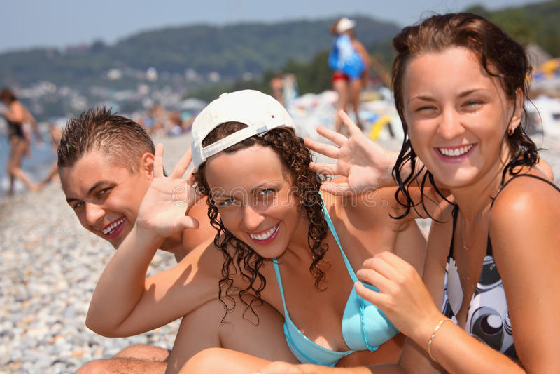 Homme de sourire et deux jeunes femmes sur la plage pierreuse photos libres de droits