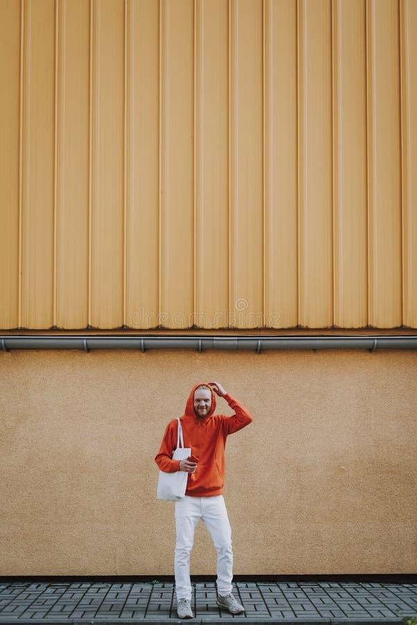 Homme de sourire heureux de hippie en ouatine rouge sur la promenade image libre de droits