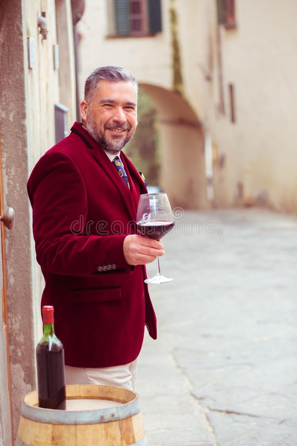 Homme de sourire heureux mûr avec le verre de vin rouge dehors dans le vieux village italien photos stock