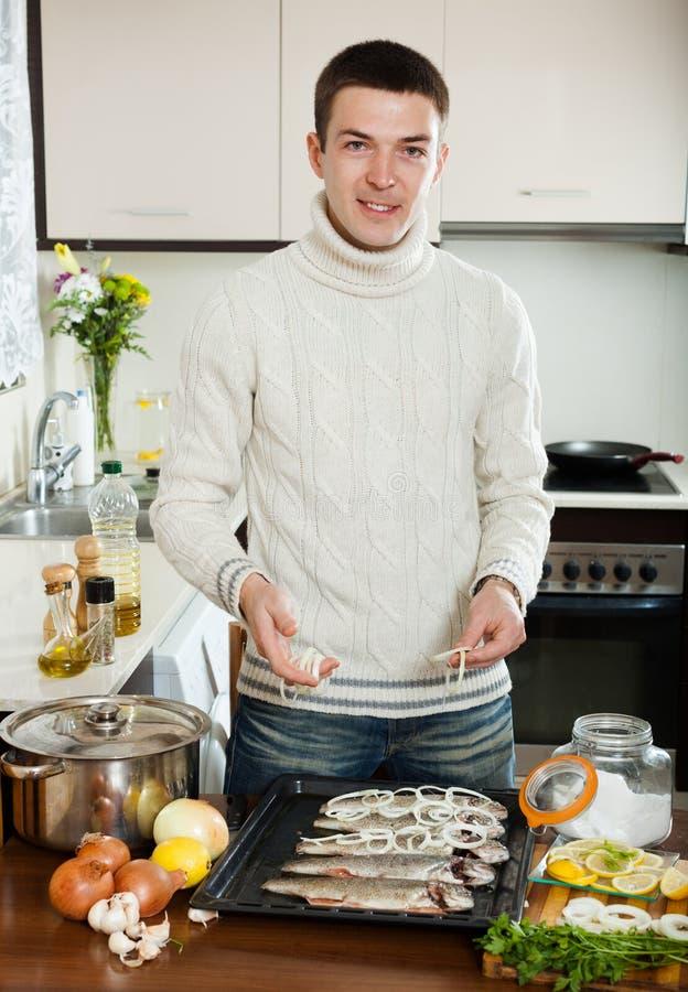 Homme de sourire mettant des morceaux d'oignon photos stock