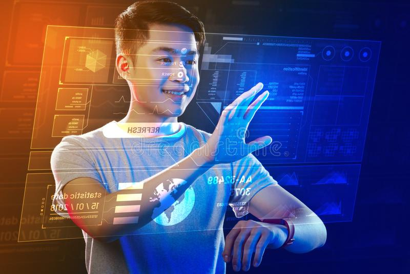 Homme de sourire mettant sa main et toucher la projection olographe photo stock