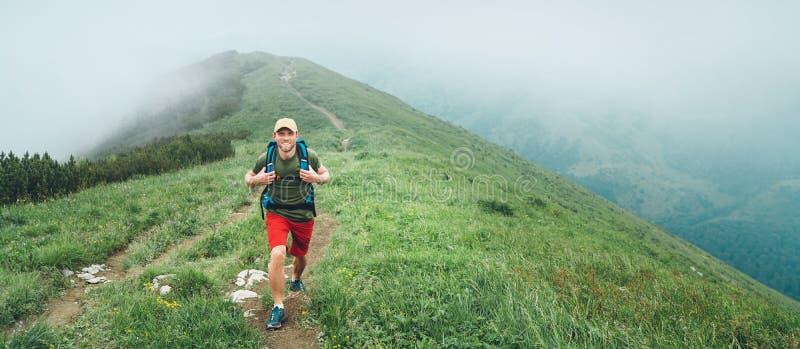 Homme de sourire de randonneur marchant par le chemin nuageux brumeux de gamme de montagne de temps avec le sac à dos Se balader  photos stock