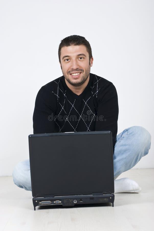 Homme de sourire s'asseyant sur l'étage avec un ordinateur portatif images libres de droits