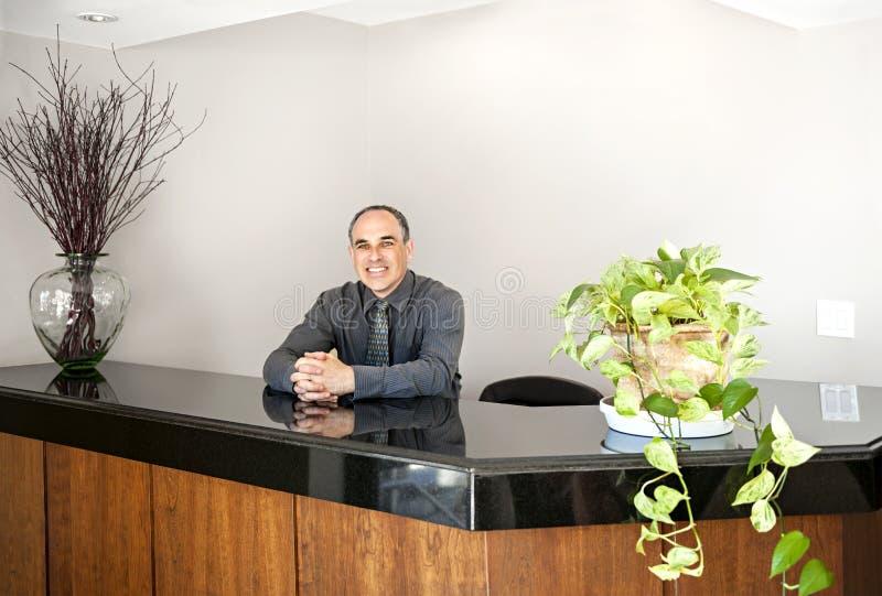 Homme de sourire se tenant à la réception de bureau photos stock