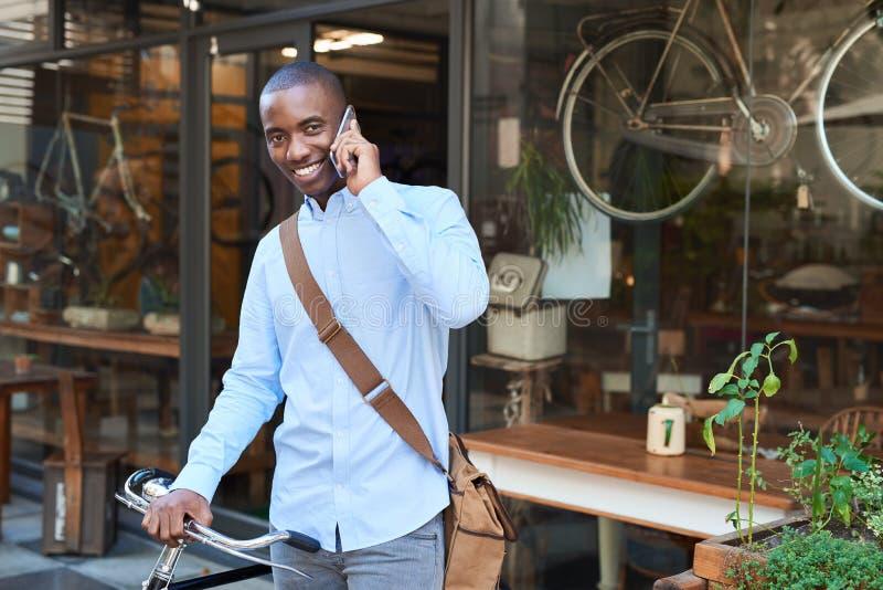 Homme de sourire se tenant avec un vélo parlant sur un téléphone portable photos libres de droits