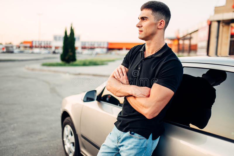 Homme de sourire se tenant près de sa voiture dehors photos stock