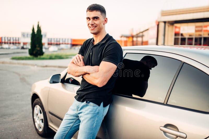 Homme de sourire se tenant près de sa voiture dehors photo libre de droits