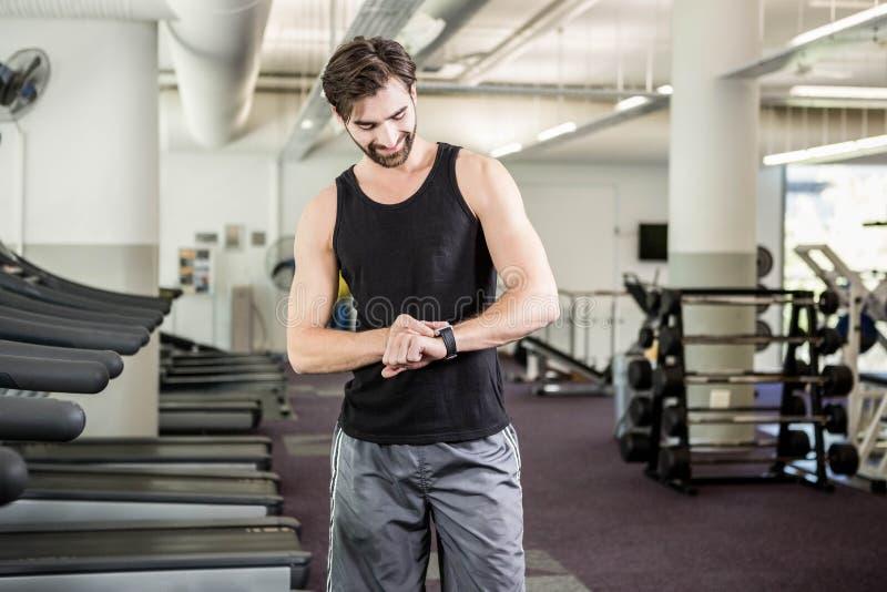 Homme de sourire sur le tapis roulant regardant le smartwatch images stock