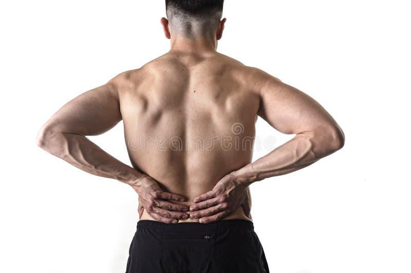 Homme de sport de corps musculaire tenant la taille lombo-sacrée endolorie massant avec sa douleur de souffrance de main image libre de droits