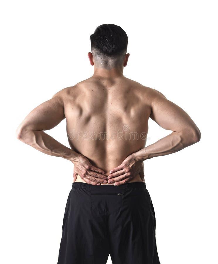 Homme de sport de corps musculaire tenant la taille lombo-sacrée endolorie massant avec sa douleur de souffrance de main photographie stock libre de droits